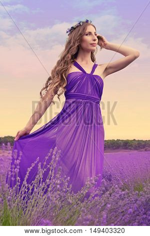 Young woman with long blonde hair in a purple dress looking at the sunset in a warm summer day in the lavender field