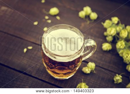 Draft Cold Beer In Glass Jar With Green Ripe Hop Cones On Black