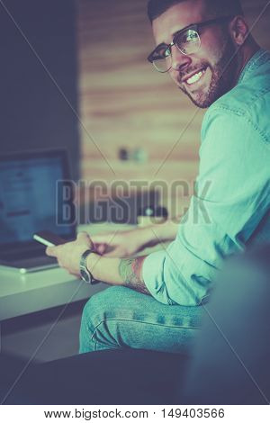 Young man using phone and works on the laptop