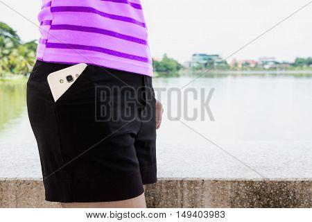 White smart mobile phone in black pocket.
