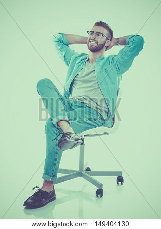 Young man sitting on the chair isolated over white background