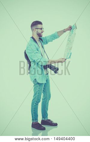 Handsome tourist looking at map isolated on white