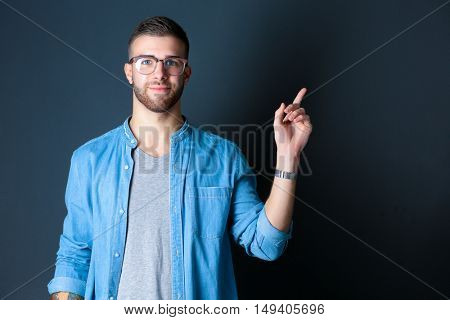 Portrait of a smiling young man pointing up