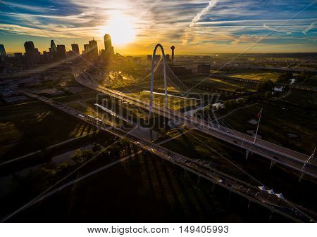 Dallas Texas Skyline Cityscape Aerial shot high above Margaret Hunt Hill Bridge on a dramatic sunrise morning casting large shadows across Trinity Overlook Park