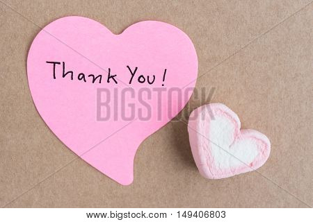 Thank you note in heart shape paper with valentines candy over brown paper