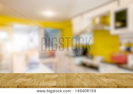 Empty wooden table and kitchen room blur background with bokeh image for product display montage.