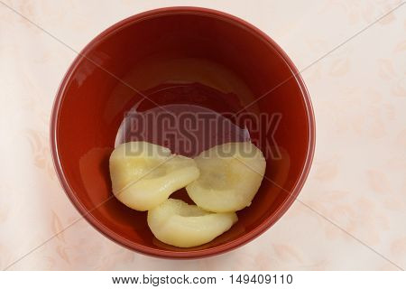 Canned sliced and pitted pears in red bowl