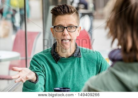Excited Woman Talking With Friend At Cafe