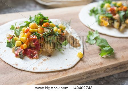 fresh Mexican tacos with chicken, vegetables, herbs and hot sauce on a wooden board, short depth of field