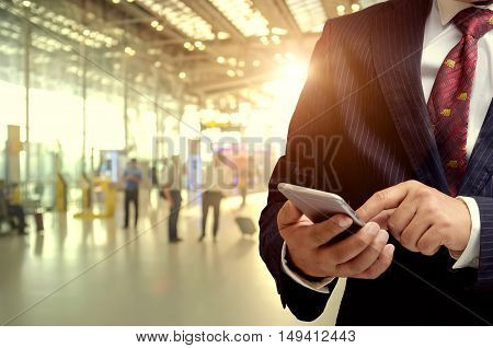Businessman hand using smartphone at Check in Counter and Passengers in a airport departure terminal.