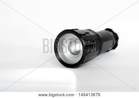 Flashlight isolated on white colored background, aluminum body, black color