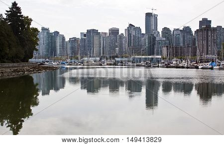Wide view of Vancouver from Stanley Park with partial view of the seawall and trees. Looking at the marina filled with yatchs and sailboats on a bright slightly overcast day with reflections.