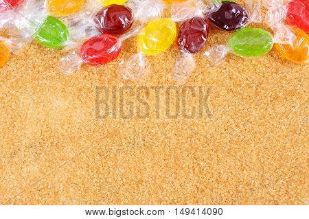 Heap of colorful candies and natural brown cane sugar diabetes and reduction eating sweets copy space for text