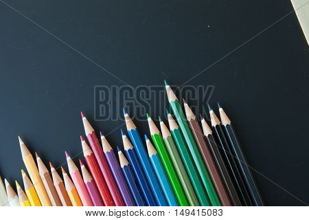 various color pencils on a blackboard background