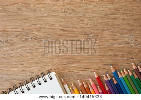 color pencils with notebook on wooden table