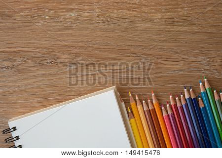 color pencils with notebook non wooden table