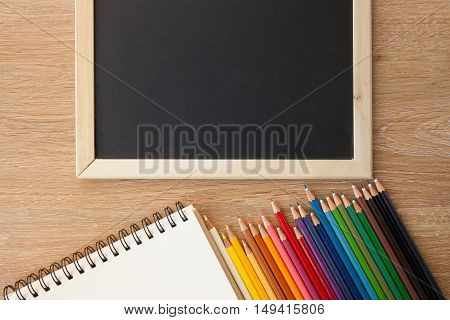 color pencils with notebook and a blackborad
