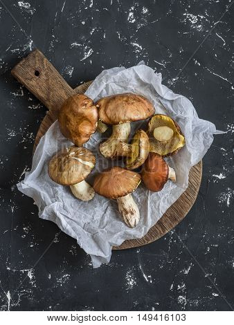 Fresh mushrooms on a wooden cutting board. On a dark background top view