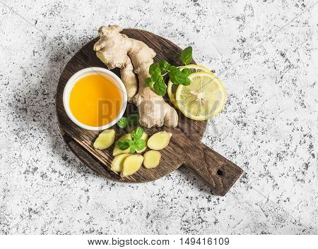 Ingredients for cooking detox drink - ginger lemon honey mint. On a light background top view
