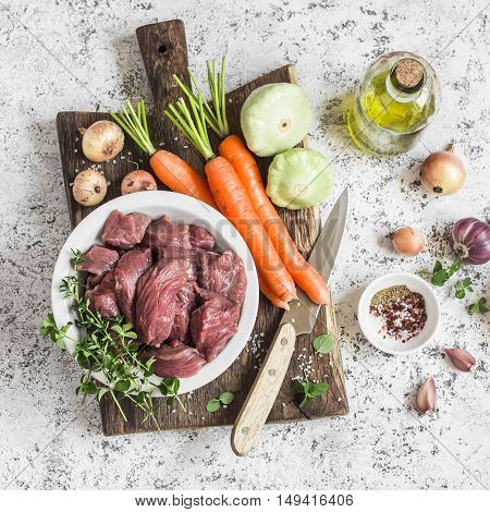 Ingredients for cooking dinner - raw beef meat carrots squashes onions garlic thyme spices olive oil. On a light background top view
