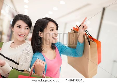 Happy women shopping in the mall and looking at something, hong kong asian