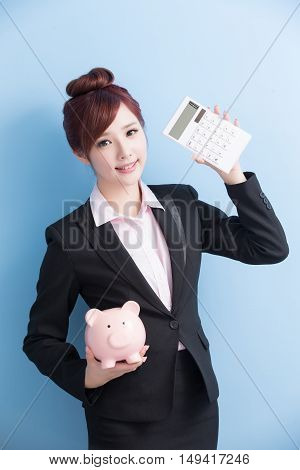 business woman take pink piggy bank and calculator smile to you with isolated on blue background