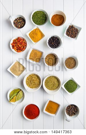 Various dried herbs and spices in ceramic bowls on kitchen table.