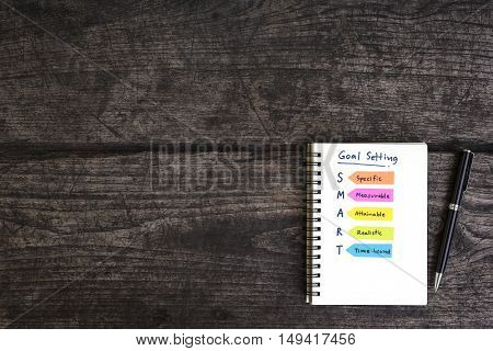 handwriting goal setting smart on open notebook with pen over grungy wooden desk business concept