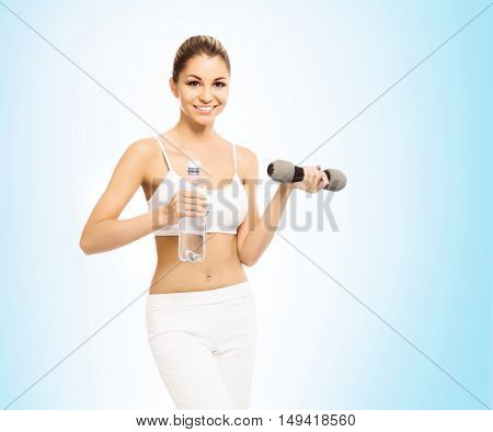 Young, sporty, fit and beautiful girl with the dumbbell over blue background. Healthy lifestyle and weight losing concept.
