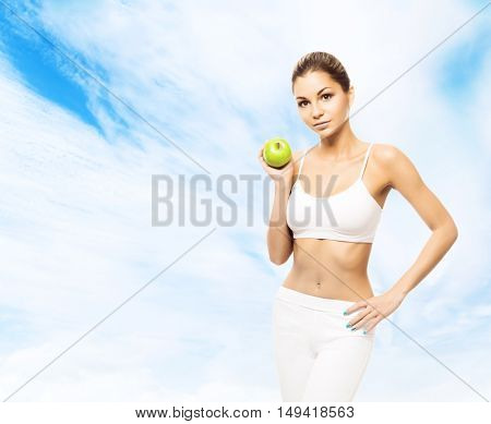 Young, sporty, fit and beautiful girl with apple over sky background. Healthy lifestyle and weight losing concept.