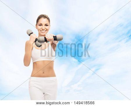 Young, sporty, fit and beautiful girl with the dumbbell over sky background. Healthy lifestyle and weight losing concept.