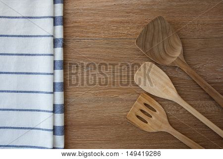 Wooden kitchen utensils and linen kitchen towels on dark wood tabletop with copy space in the center