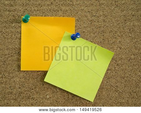 Orange and green sticky notes pinned on brown corkboard