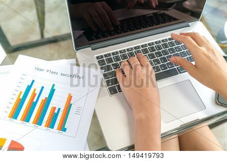 Business woman hand with Financial charts and laptop on the table