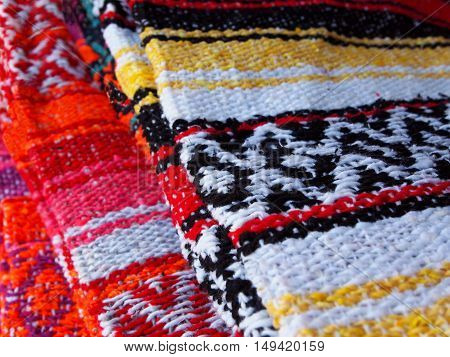 A stack of traditional woven cotton or acrylic blankets from Latin America in rainbow of bright vibrant colors.