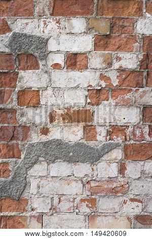 Old vintage red brick wall with white plaster texture background. Vertical image