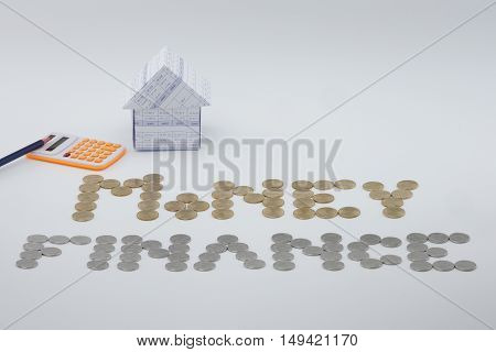 House With Gold And Silver Coins With Pencil And Calculator
