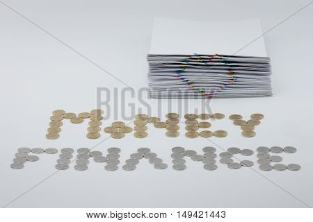 Pile overload paperwork with colorful heart-shaped paperclip with gold and silver coins on white background.