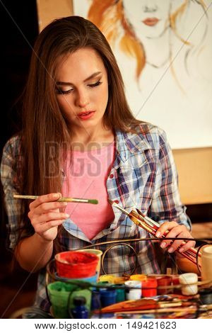 Girl artist whith paints portrait of woman with pencil. Girl painter look down. Girl paints by panting brush on easel.