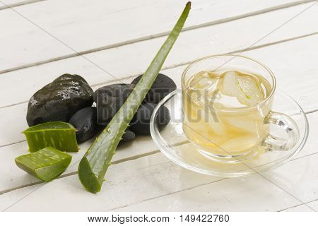 Aloe Vera Herbal and Aloe Vera  juice and slice on plate with black rock on wooden white background.Top view and close up.001
