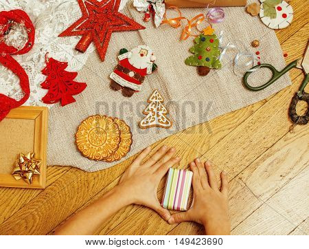 handmade christmas gifts in mess with toys, candles, fir, ribbon, tree cone wooden vintage, post card view, child hand