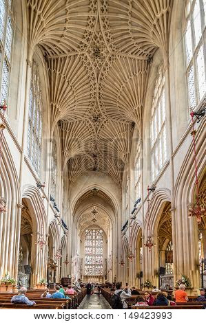 Bath UK - August 15 2015: Interior of Bath Abbey with interior view with faithful praying . The abbey is an Anglican parish church and an active place of worship