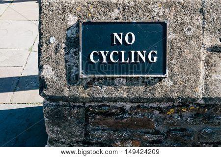 No cycling sign in a stone wall