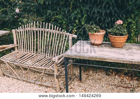 Bench and Flower pots with plants on a wooden table in the home garden