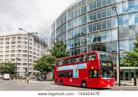 LONDON UK - AUGUST 21 2015: Cheapside street in London with a red bus and St. Pauls Cathedral reflected on a modern glass facade.