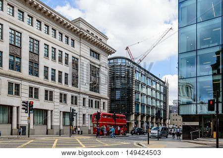 LONDON UK - AUGUST 21 2015: Cannon street in London with a red bus and people crossing the street while St. Pauls Cathedral is reflected on a modern glass facade.