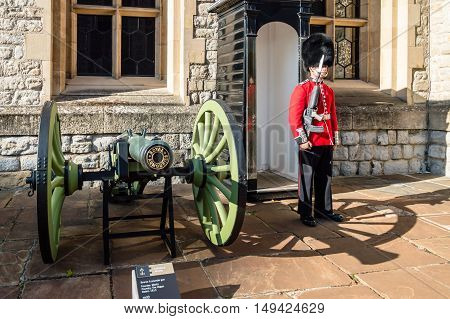 LONDON UK - AUGUST 21 2015: Queen's Guard and gun - Tower of London. The Queen's Guard is the contingents of infantry and cavalry soldiers charged with guarding the official royal residences in the United Kingdom.