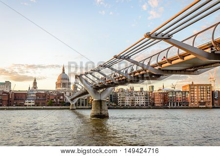 LONDON UK - AUGUST 21 2015: Millenium Bridge and London waterfront with St Pauls Cathedral. Millenium Bridge was designed by architect Norman Foster