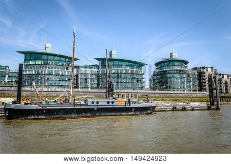 LONDON UK - AUGUST 22 2015: Modern housing and boat in London riverside near Tower Bridge