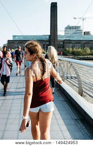 LONDON UK - AUGUST 22 2015: Girl and other people walking over Millennium bridge a sunny day. Tate Modern in the background.